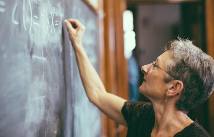 mathemathics-professor-at-chalkboard-writing-formula-picture-id511026368